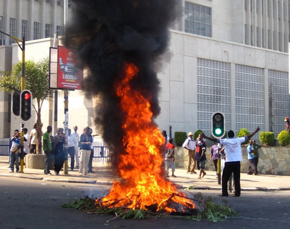 A protester burns vegetation in a street in Lilongwe, Malawi, Wednesday, July 20, 2011. Protesters went on the rampage after a court injunction stopped them protesting the economic and democratic crisis in the country. A coalition of more than 80 rights groups had organised nationwide protest marches for Wednesday. They wanted to protest what they say are moves by the Malawi's President Bingu wa Mutharika to roll back hard-fought democratic gains made since the first democratic polls in 1994 removed dictator Kamuzu Banda from power. (AP Photo/Diane Boles)