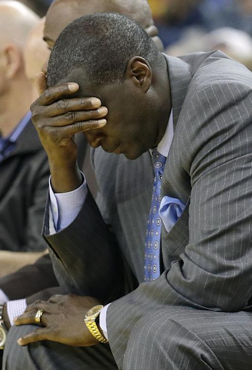 Utah Jazz head coach Tyrone Corbin covers his face as he sits on the bench during the third quarter of an NBA basketball game against the Golden State Warriors in Oakland, Calif., Saturday, Nov. 16, 2