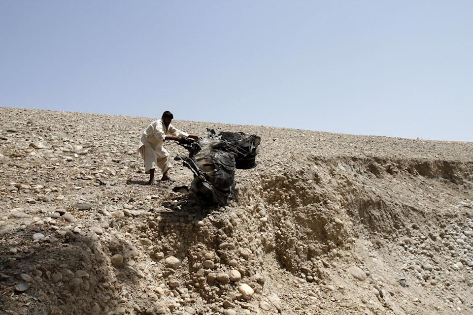 An Afghan man pushes parts  of a destroyed vehicle off a hill after a roadside explosion on the outskirts of Laghman province east of Kabul, Afghanistan, Sunday, Aug. 12, 2012. A provincial spokesman says a roadside bomb has killed a district chief in eastern Afghanistan and three of his bodyguards. (AP Photo/Rahmat Gul)