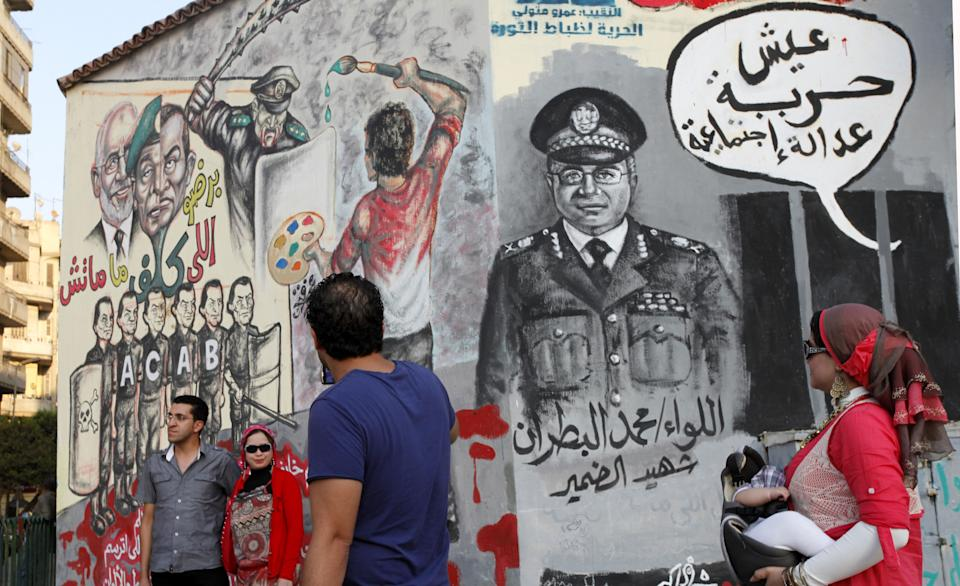 "Egyptian woman carries her baby passes by a new mural on a recently whitewashed wall while others taking photos near it,  in Tahrir Square, Cairo, Egypt, Friday, Sept. 28, 2012. Arabic writing in the thought bubble reads "" Live freedom , social justice."" (AP photo/Mohammad Hannon)"