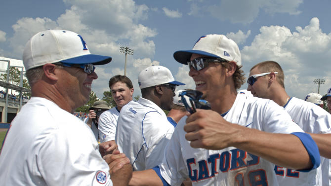 Florida coach Kevin O'Sullivan, left, congratulates Tyler Thompson (18) after the Gators of Florida defeated Mississippi State 8-6 during the third round of the NCAA college Super Regional baseball tournament in Gainesville, Fla., Sunday, June 12, 2011. (AP Photo/Phil Sandlin)