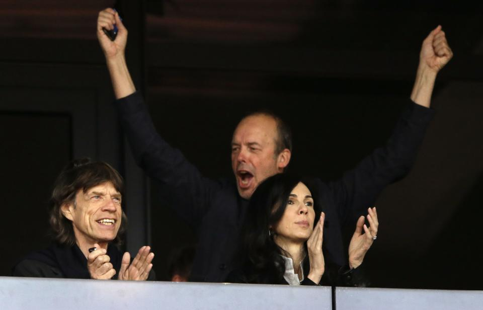 Musician Mick Jagger, left, watches an evening session of athletics competition with L'Wren Scott, right, in the Olympic Stadium at the 2012 Summer Olympics, Monday, Aug. 6, 2012, in London. (AP Photo/Matt Slocum)