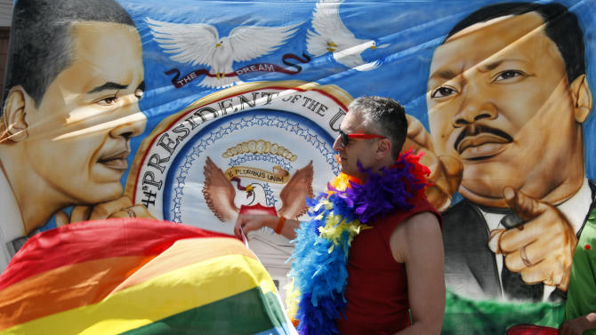 Trenton Garris waves his rainbow flag in front of a banner in support of President Barack Obama who was visiting the Paramount Theater one day after announcing his support for same sex marriage, in Seattle on Thursday, May 10, 2012. (AP Photo/Kevin P. Casey)