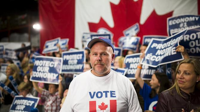 A supporter poses before Canada's PM and Conservative leader Harper's campaign rally in London