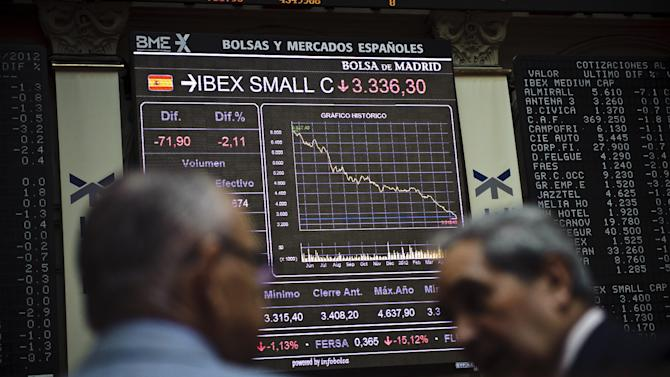 Brokers looks at the main display at the Stock Exchange in Madrid, Wednesday, May 16, 2012. Spain's Prime Minister warned that the country faced the real danger of being locked out of international markets as investors continued to fret about the future of the euro. At one stage, the difference between the interest rates demanded by investors for Spanish and German 10-year bonds shot past the 500 basis point level, prompting Mariano Rajoy's warning over the country's ability to continue funding itself. (AP Photo/Daniel Ochoa de Olza)