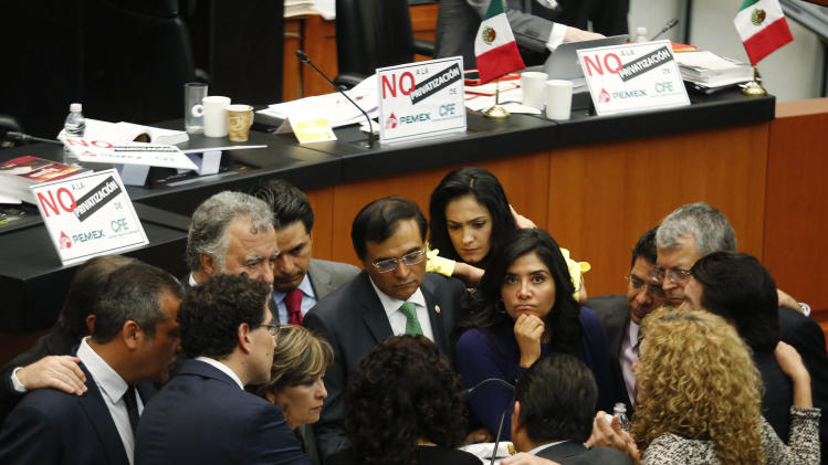 Senators of the PRD speak near placards in the background while interrupting a debate on an energy reform bill at the Senate in Mexico City
