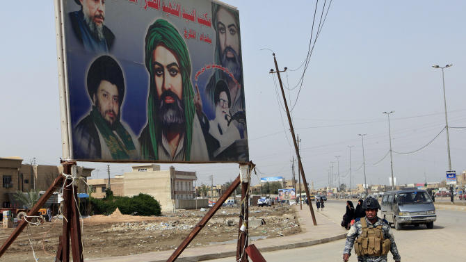 """In this Sunday, Feb. 24, 2013 photo, an Iraqi policeman walks past a sign showing Shiite religious leaders and Shiite's who were killed during a fight between US troops and al-Mahdi Army militia in the Jihad neighborhood of west Baghdad, Iraq. The fliers claiming to be from a new Iranian-linked Shiite militant group began turning up last week in front of Iraqi Sunni households bearing a chilling message: Get out now or face """"great agony"""" soon.   (AP Photo/ Karim Kadim)"""