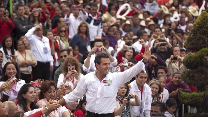 Presidential candidate Enrique Pena Nieto, of the Institutional Revolutionary Party, center, waves to supporters during a campaign rally in Atlacomulco, Mexico, Sunday, June 17, 2012. Mexico will hold presidential elections on July 1. (AP Photo/Alexandre Meneghini)