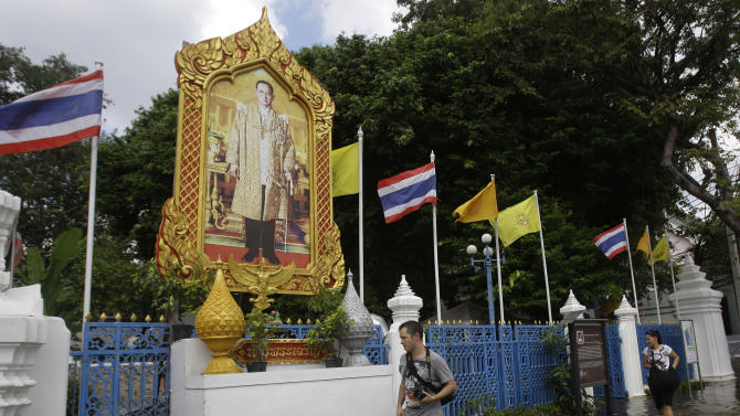 Foreigners walk in front of a picture of Thai King Bhumibol Adulyadej along a flooded road in Bangkok, Thailand, Sunday, Oct. 30, 2011. City dikes overflowed in at least two places as coastal high tides pushed up the main Chao Praya river from the Gulf of Thailand, with water spilling into streets as city workers and troops shored up concrete walls with sandbags. (AP Photo/Aaron Favila)