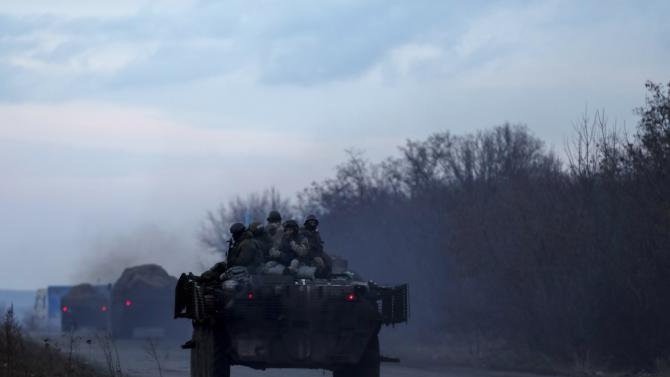 Members of the Ukrainian armed forces ride on an armoured personnel carrier as they guard a convoy of multiple rocket launcher systems belonging to the Ukrainian armed forces near Kramatorsk