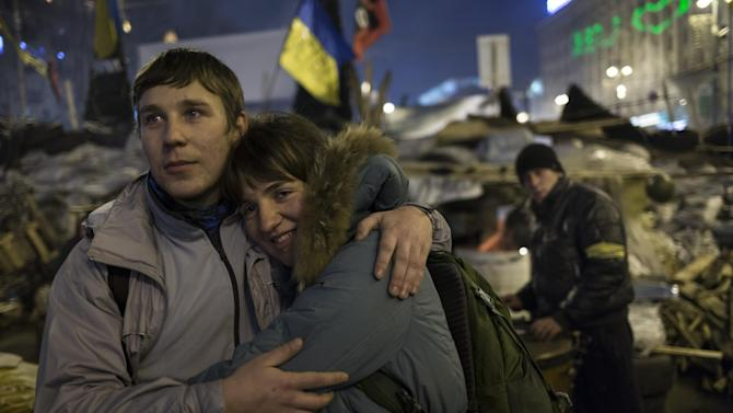 """A young couple embrace each other as they look at the stage during a concert after a pro-European Union rally in the Independence Square in Kiev, Ukraine, Wednesday, Dec. 18, 2013. Putin and Yanukovych both pledged Tuesday, Dec. 17, 2013 to boost economic and trade ties to expand the """"strategic partnership"""" between the two neighbors. (AP Photo/Alexander Zemlianichenko)"""