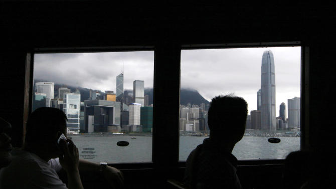 Passengers look out through the window in a ferry in Hong Kong Tuesday, June 11, 2013. Edward Snowden, an American defense contractor who said he leaked information on classified U.S. surveillance programs, could benefit from a quirk in Hong Kong law that would ensure a lengthy battle to deport him. (AP Photo/Kin Cheung)