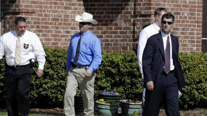 Law enforcement officials walk out of the home of Kaufman District Attorney Mike McLelland Monday, April 1, 2013, near Forney, Texas. McLelland and his wife were murdered on Saturday at their home. (AP Photo/Tony Gutierrez)