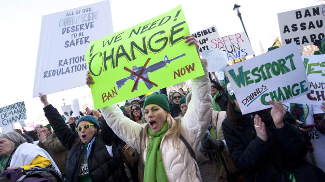 Demonstrators yell and hold up signs during a rally at the Capitol in Hartford, Conn., Thursday, Feb. 14, 2013. Thousands of people turned out to call on lawmakers to toughen gun laws in light of the December elementary school shooting in Newtown that left 26 students and educators dead. (AP Photo/Jessica Hill)