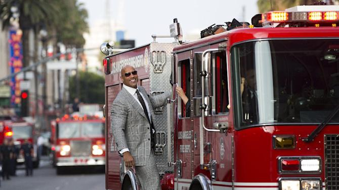 "Cast member Johnson rides a Los Angeles Fire Department engine as he arrives at the premiere of ""San Andreas"" in Hollywood"