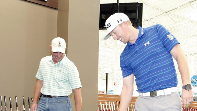Golf Galaxy customer Kelly Sargent, left, and PGA Tour professional Hunter Mahan retrieve their golf balls during a friendly putting competition at Golf Galaxy's grand opening in Grapevine, Texas, on Friday, November 9, 2012. (Brandon Wade/AP Images for Golf Galaxy)