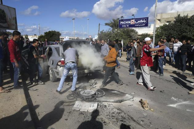People surround wreckage of car after a bomb exploded inside the vehicle in Benghazi