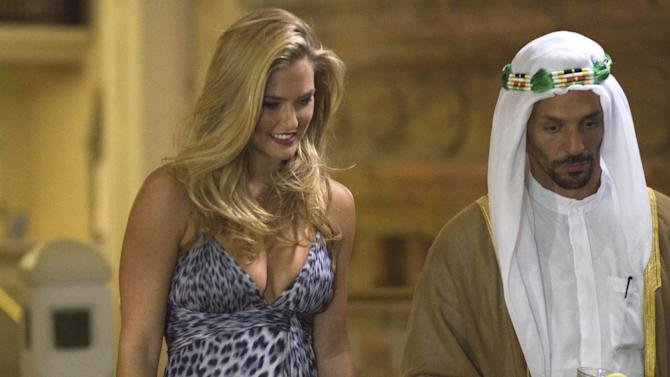 In this May 1, 2012 photo, Israeli model Bar Refaeli plays a seductress with actor Tomer Sisley on a film set in Eilat, southern Israel. The brazen 2010 assassination of a Hamas operative in Dubai remains shrouded in mystery, but an upcoming film is offering its own comedic interpretation of the movie-like events, complete with a gang of small-time crooks and a sly seductress played by Refaeli. (AP Photo/Dan Balilty)