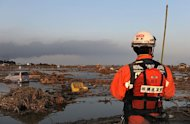A Japanese rescuer looks at a land devastated by the tsunami in Sendai. Japan raced to avert a meltdown of two reactors at a quake-hit nuclear plant Monday as the death toll from the disaster on the ravaged northeast coast was forecast to exceed 10,000