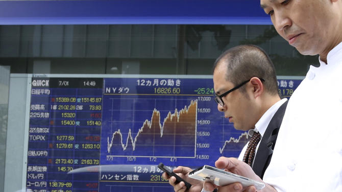 Passers-by use cellphones in front of electronic stock board of a securities firm in Tokyo, Tuesday, July 1, 2014. Shares were mostly lower in Asia on Tuesday as investors shrugged off signs that Chinese manufacturing is regaining momentum. (AP Photo/Koji Sasahara)
