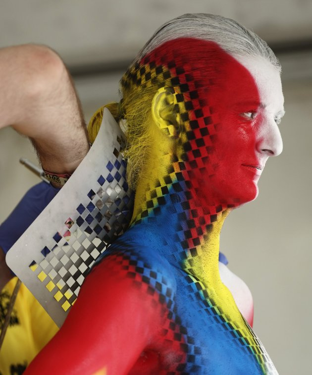 An artist airbrushes a design on a model during the annual World Bodypainting Festival in Poertschach