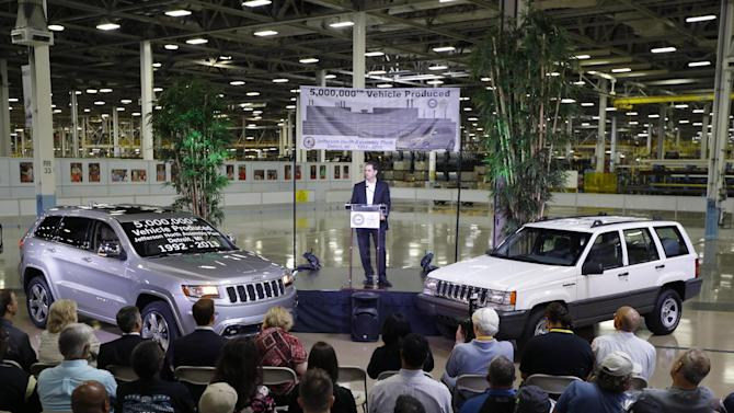FILE - In this Aug. 13, 2013 file photo, Scott Garberding, senior vice president of manufacturing for Chrysler Group LLC stands between a 1992 Grand Cherokee, right, and the automaker's 5,000,000th vehicle produced at the Jefferson North Assembly Plant in Detroit. Chrysler's U.S. sales rose 12 percent in August as strong truck sales pushed the company to its best month in six years. (AP Photo/Carlos Osorio, File)