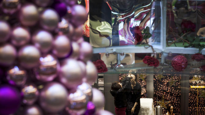 A woman dresses up a mannequin at a fashion boutique inside a shopping mall in Beijing Monday, Dec. 17, 2012. China's new Communist Party leaders are promising reforms aimed at reducing reliance on exports to drive growth and more spending if needed to prop up a shaky economic recovery. (AP Photo/Andy Wong)