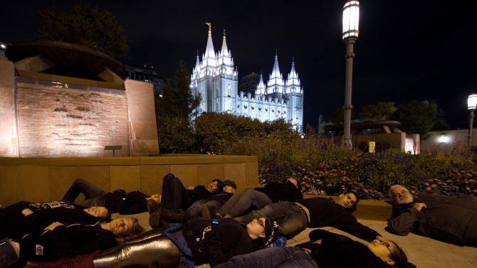 FILE - In this Oct. 7, 2010 photo, Gay rights activist lay on the sidewalk near The Church of Jesus Christ of Latter-day Saints' temple  in Salt Lake City.  A sermon by a high-ranking church official on Oct. 3 denouncing homosexual attraction as unnatural and immoral exacerbated the troubled relationship with many lesbian, gay, bixsexual and transgender Mormons who have come out.  Mormon-based gay activists said the sermon was also dangerous, coming as it did in the midst of the national furor over a Rutgers University student who jumped to his death.  (AP Photo/Jim Urquhart)