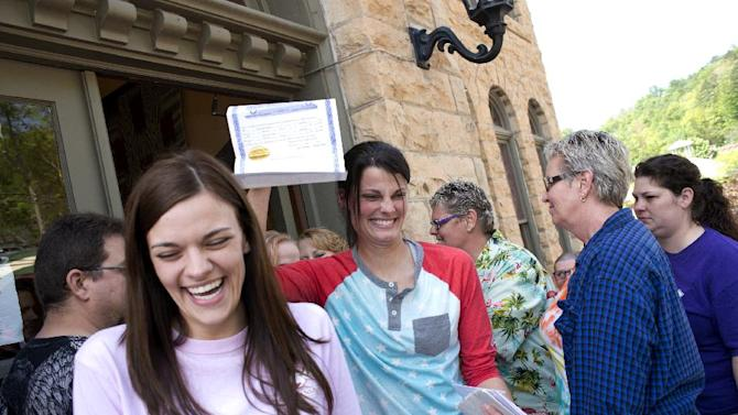 FILE - In this May 10, 2014 file photo, Kristin Seaton, center, of Jacksonville, Ark., holds up her marriage license as she leaves the Carroll County Courthouse in Eureka Springs, Ark., with her partner, Jennifer Rambo, left, of Fort Smith, Ark., in Eureka Springs, Ark. The Arkansas Supreme Court has rejected the state attorney general's request for a stay of a judge's ruling that overturned Arkansas' constitutional ban on gay marriage, Wednesday, May 14, 2014. (AP Photo/Sarah Bentham, file)