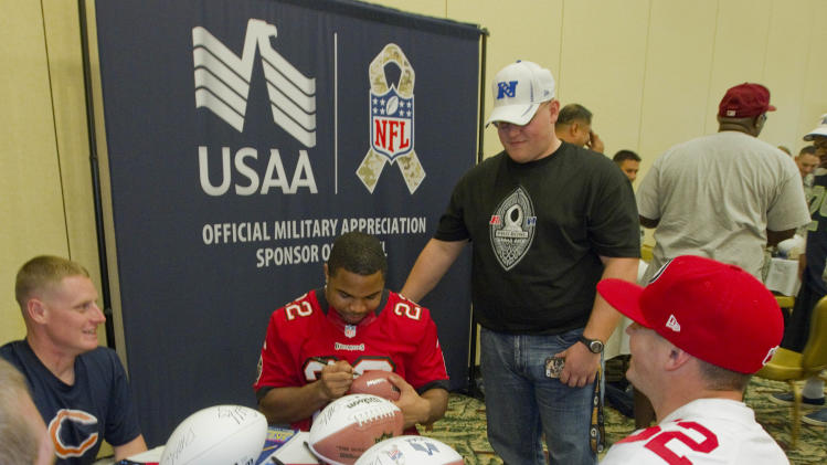 In this photo provided by IMG Consulting, Wounded United States Army soldiers Timothy Adams, left center, Jonathon Carpenter, standing top right center, and Michael Cagle, far right, all members of the Warrior Transition Battalion look on as Tampa Bay Buccaneers running back Doug Martin autographs a football at Schofield Barracks Thursday, Jan. 24, 2013, in Honolulu. Several NFL All-Star football players joined members of the Warrior Transition Battalion for lunch and a autograph session. (Eugene Tanner/AP Images for USAA. IMG Consulting