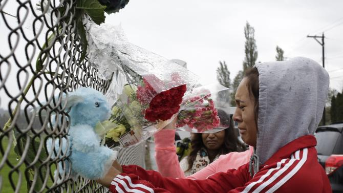 Student Tyanna Davis cries after placing flowers on a fence outside Marysville-Pilchuck High School in Marysville, Washington