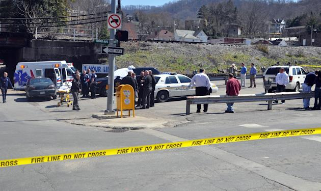 Law enforcement officers and emergency service personnel converge on the scene of the shooting in downtown Williamson, W.Va., Wednesday, April 3, 2013, where Sheriff Eugene Crum was shot and killed at