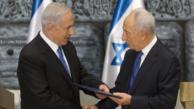 Israeli Prime Minister Benjamin Netanyahu, left, receives a folder from Israeli President Simon Peres in a brief ceremony in the president's Jerusalem residence Saturday, Feb. 2, 2013.  Israel's president has asked Netanyahu to form the next government, and Netanyahu says he wants to advance peace talks with the Palestinians. (AP Photo/Jim Hollander, Pool)