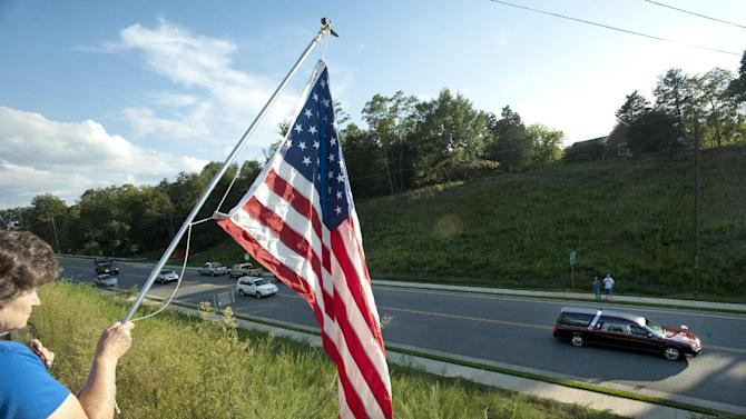 FILE - In this Monday, Aug. 27, 2012 file photo, Sue Funderburk holds a U.S. flag as she pays her respects for Marine Staff Sgt. Greg Copes of Lynch Station,Va. as the procession for his funeral heads to his burial site in Altavista, Va. So far, 1,980 American soldiers have been killed in Afghanistan. A recent surge of insider attacks by Afghan security forces has claimed the lives of 40 allied soldiers, according to a report by the Brookings Institution. Americans may have pushed the war from their everyday consciousness. But losing neighbors and classmates keeps turning a distant war into an anguished and very personal reality. (AP Photo/The News & Advance, Jill Nance)