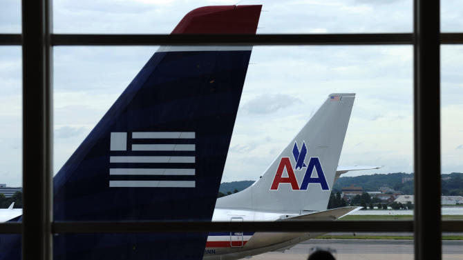 FILE- In this Tuesday, Aug. 13, 2013, file photo, an American Airlines plane and a US Airways plane are parked at Washington's Ronald Reagan National Airport in Washington.American Airlines reports quarterly earnings on Tuesday, Jan. 28, 2014. (AP Photo/Susan Walsh, File)
