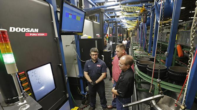 In this Friday, Jan. 11, 2013, photo, Webb Wheel Products employees watch as the Doosan V550M drills holes in one side of a 130-lb CK drum without help from humans at Webb Wheel Products in Cullman, Ala. Webb Wheel hasn't added a factory worker in three years, though it's making 300,000 more drums annually, a 25 percent increase, because of robots. (AP Photo/Dave Martin)