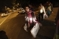 Polling officers carry electronic voting machines (EVM) as they leave a polling station at the end of polls, during the state assembly election in New Delhi December 4, 2013. REUTERS/Adnan Abidi