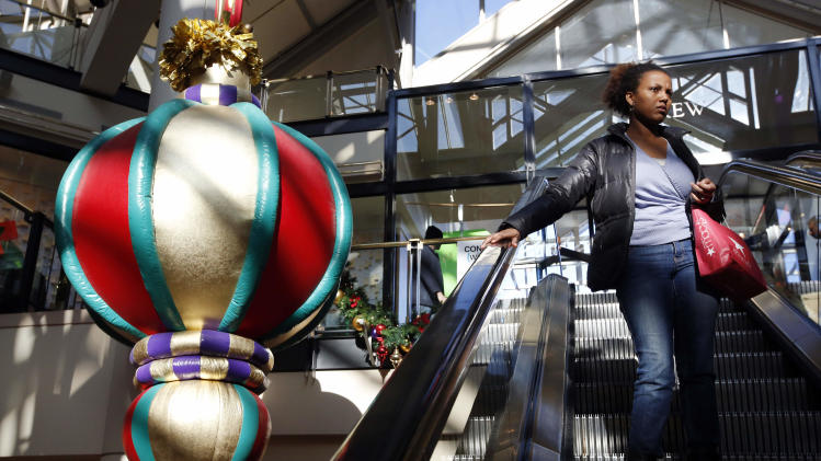 """A woman rides the escalator past a giant holiday ornament at the CambridgeSide Galleria mall in Cambridge, Mass., Monday, Dec. 24, 2012. Although fresh data on the holiday shopping season is expected in coming days, early figures point to a ho-hum season for retailers despite last-ditch efforts to lure shoppers over the final weekend before Christmas. And with concerns about the economy and the looming """"fiscal cliff"""" weighing on the minds of already cautious shoppers, analyst say stores will need to offer """"once in a lifetime"""" blowouts to clear out inventory.  (AP Photo/Michael Dwyer)"""