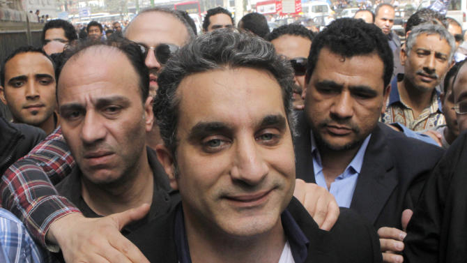 A bodyguard secures  popular Egyptian television satirist Bassem Youssef, who has come to be known as Egypt's Jon Stewart, as he enters Egypt's state prosecutors office to face accusations of insulting Islam and the country's Islamist leader in Cairo, Egypt, Sunday, March 31, 2013. Government opponents said the warrant against such a high profile figure, known for lampooning President Mohammed Morsi and the new Islamist political class, was an escalation in a campaign to intimidate critics. (AP Photo/Amr Nabil)