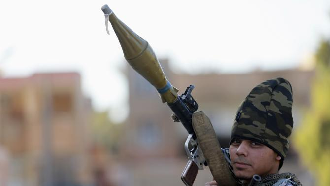 A personnel of pro-government Libyan forces, who are backed by locals, holds a RPG during clashes in Benghazi