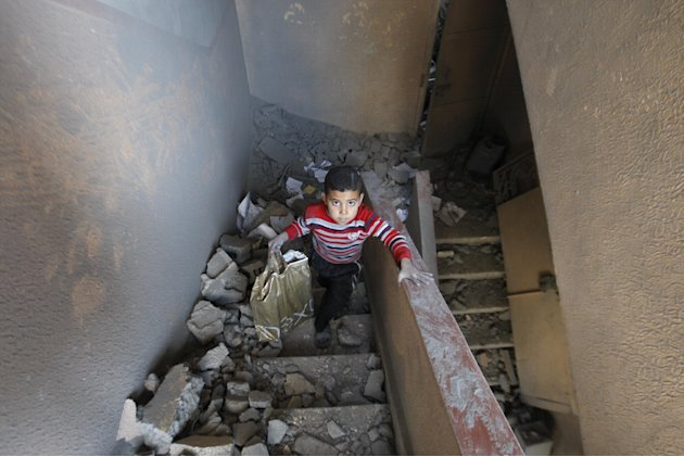 A Palestinian boy walks up the stairs of a house destroyed on Sunday by an Israeli strike in Gaza City, Monday, Nov. 19, 2012. The Palestinian civilian death toll mounted Monday as Israeli aircraft st