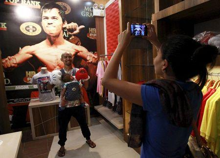 Woman uses a mobile phone to take pictures of her husband posing in front of a poster of boxer Manny Pacquiao of the Philippines on display at a mall in Manila