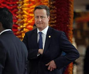 Britain's PM Cameron reaches into his pocket as he arrives for official photograph of Commonwealth heads of states during the CHOGM opening ceremony in Colombo