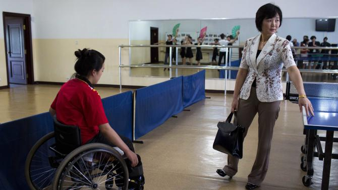 "In this June 13, 2012 photo, North Korean Li Pun Hui stands next to a ping pong table as a Paralympic table tennis player passes by in her wheelchair at the Taedonggong Cultural Center for the Disabled in Pyongyang, North Korea.  Putting aside politics, the intensely competitive Li paired up with her arch rival, South Korean star Hyun Jung-hwa, in 1991 as part of the first ""unified Korea"" team to march into international competition wearing the flag of the Korean Peninsula. (AP Photo/David Guttenfelder)"