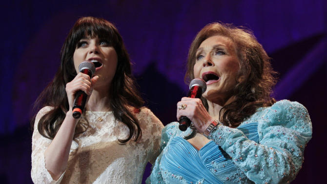 "Country music star Loretta Lynn, right, and actress Zooey Deschanel sing Lynn's hit ""Coal Miner's Daughter"" during a performance of the Grand Ole Opry on Thursday, May 10, 2012, in Nashville, Tenn. During her appearance on the show, Lynn announced that a musical of ""Coal Miner's Daughter"" is in development and Deschanel will play her. (AP Photo/Mark Humphrey)"