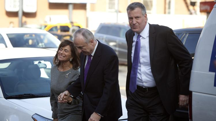 Newly appointed New York City Police Commissioner Bratton, his wife Rikki and mayor-elect de Blasio arrive for a tribute service for Nelson Mandela at the National Action Network's headquarters in New York