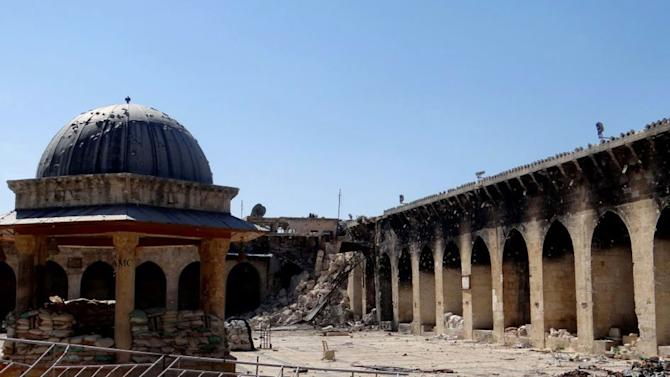 This journalism image provided by Aleppo Media Center AMC which has been authenticated based on its contents and other AP reporting, shows the damaged famed 12th century Umayyad mosque without the minaret, background right corner, which was destroyed by the shelling, in the northern city of Aleppo, Syria, Wednesday April 24, 2013. The minaret of a famed 12th century Sunni mosque in the northern Syrian city of Aleppo was destroyed Wednesday, leaving the once-soaring stone tower a pile of rubble and twisted metal scattered in the tiled courtyard. President Bashar Assad's regime and anti-government activists traded blame for the attack against the Umayyad mosque, which occurred in the heart Aleppo's walled Old City, a UNESCO World Heritage site. It was the second time in just over a week that a historic Sunni mosque in Syria has been seriously damaged. (AP Photo/Aleppo Media Center, AMC)