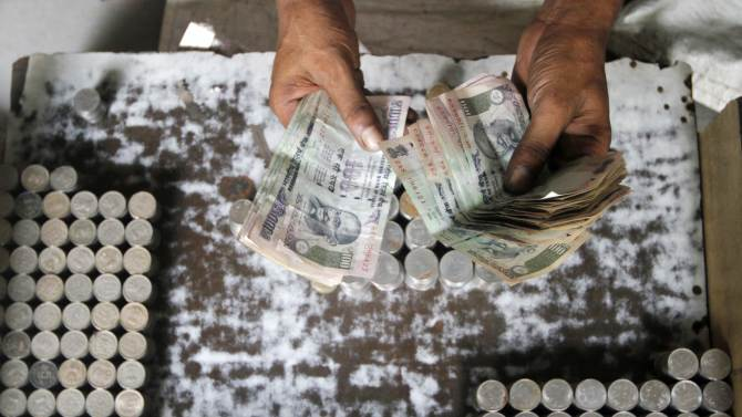 A man exchanging damaged Indian currency counts 100 rupee notes along a roadside in Kolkata