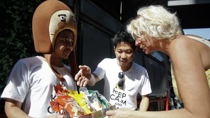 "Packets of ""HiSo""snacks are offered to foreign tourists during a promotion event in central Bangkok"
