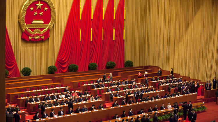 Delegates line up to cast their ballots during a plenary session of the National People's Congress held in Beijing's Great Hall of the People Thursday, March 14, 2013. China's new leader Xi Jinping capped his rise Thursday by adding the largely ceremonial title of president, though he will need cautious maneuvering to consolidate his power and build support from a public that is increasingly clamoring for change. (AP Photo/Alexander F. Yuan)